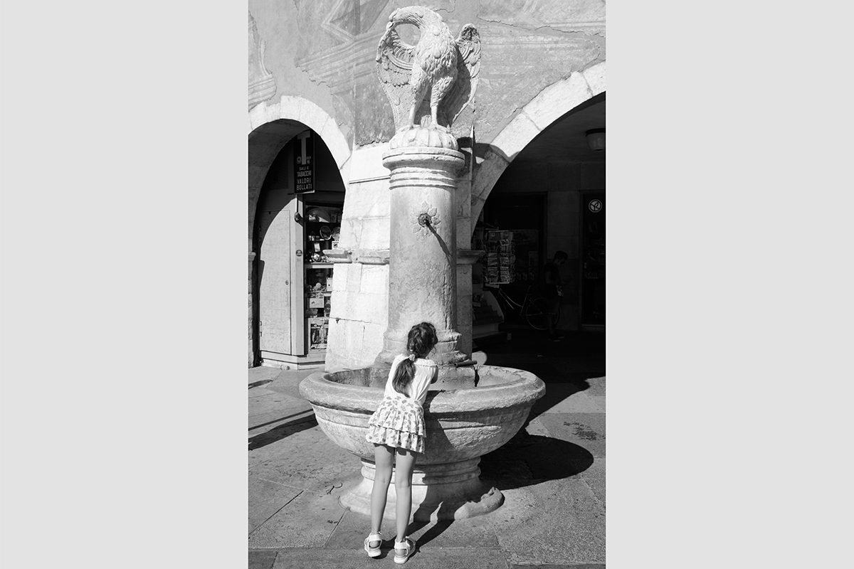 A girl drinking at a fountain, Piazza Duomo, Trento, Italy, 2016.  Photograph by David Rowley